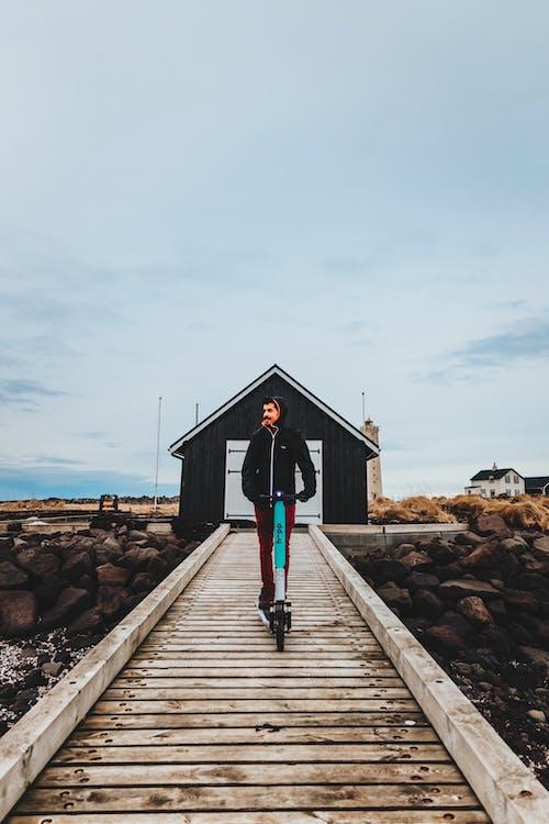 Woman in Black Dress Standing on Wooden Dock