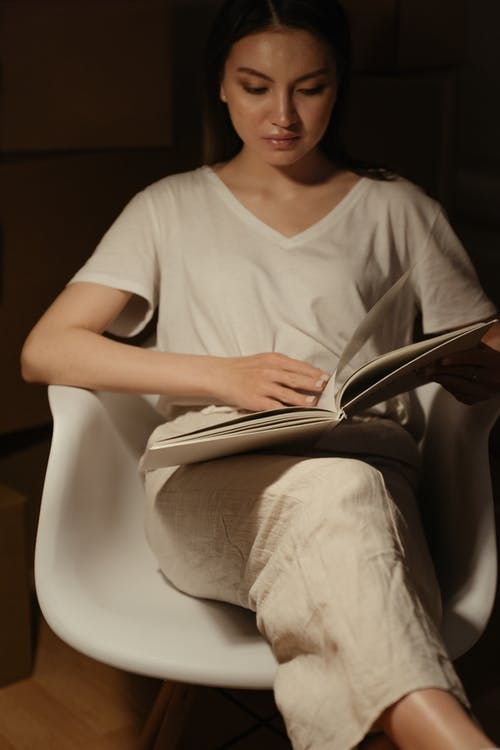 Woman in White V Neck T-shirt Sitting on White Chair