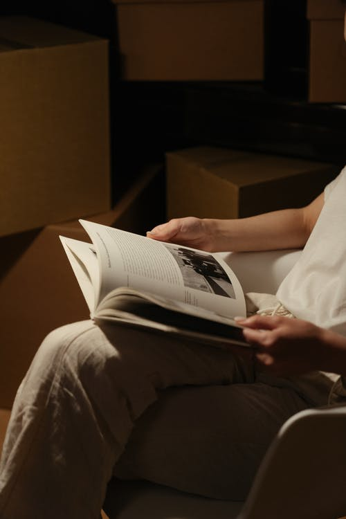 Person in White Shirt and Gray Pants Reading Book