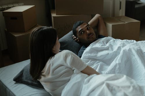 Man in White T-shirt Lying on Bed Beside Woman in Gray Shirt