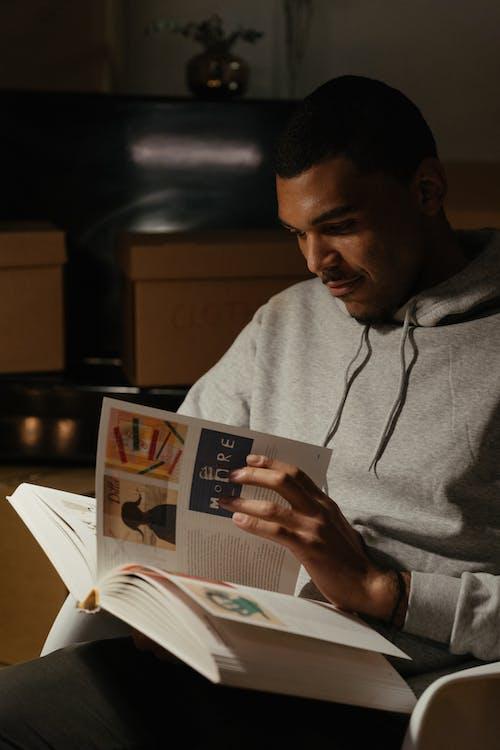 Man in Gray Hoodie Reading Newspaper
