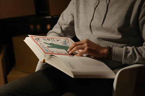 Person in Gray Hoodie Reading Book