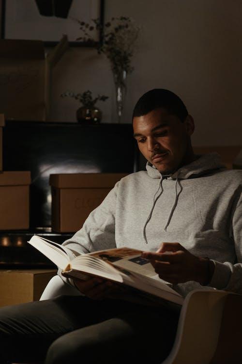 Man in Gray Hoodie Reading Book