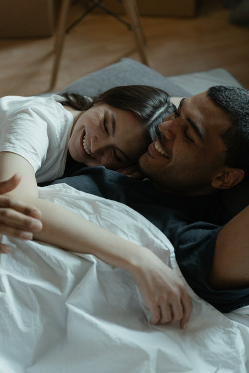 Man in White T-shirt Lying on Bed Beside Woman in White T-shirt