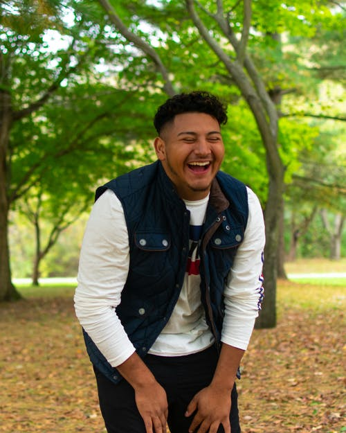 Cheerful young ethnic male in casual clothes laughing with closed eyes while resting in park on autumn day