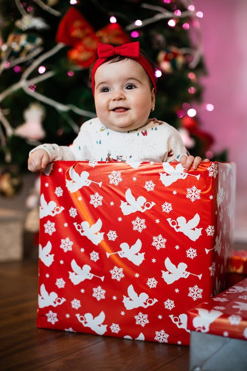 Adorable chunky baby girl with red bow on head sitting on floor behind wrapped gift box near decorated Christmas tree and smiling