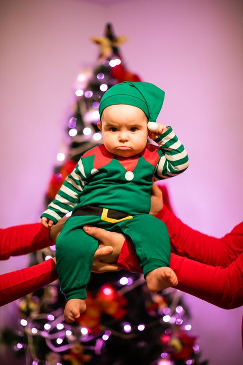 Adorable child in Santa Claus clothes near Christmas tree