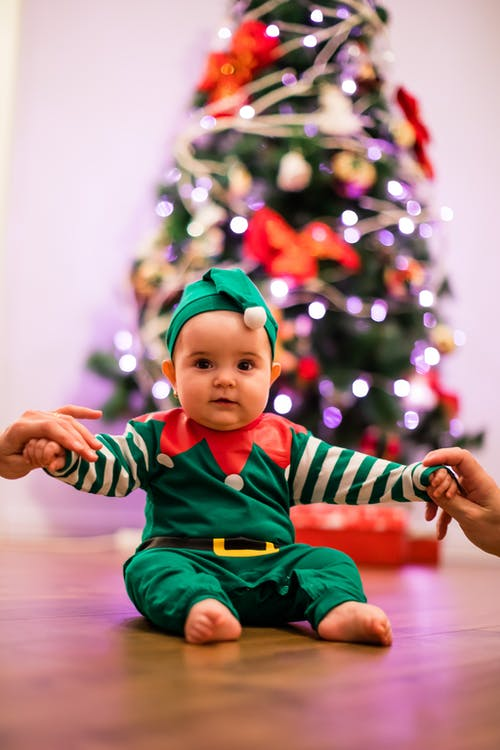 Cute baby sitting on floor in elf costume during Christmas celebration