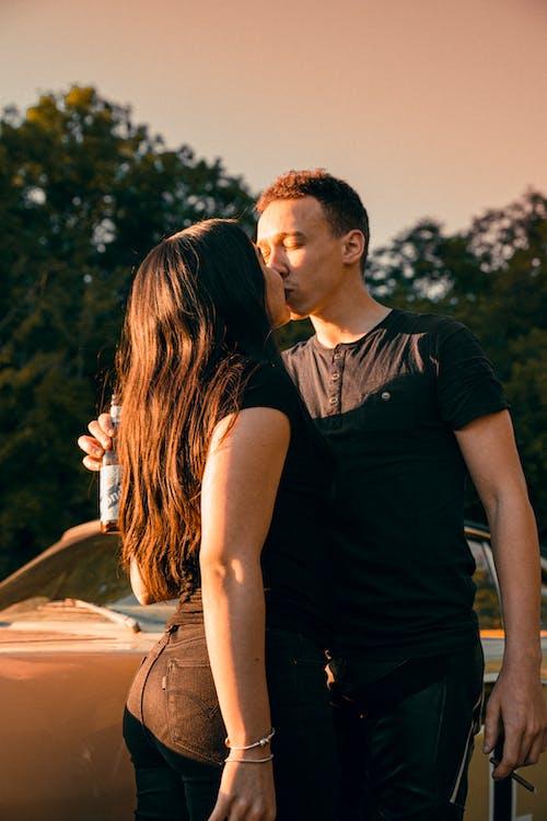 Man in Black Crew Neck T-shirt Kissing Woman in Black Dress