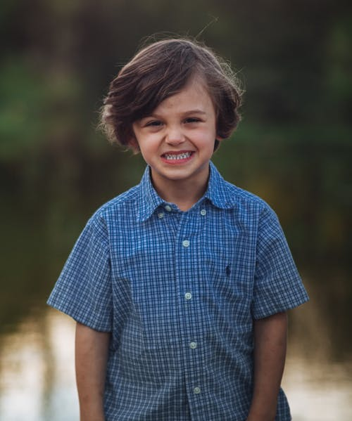 Funny child smiling while resting near pond