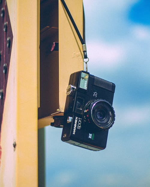 Retro photo camera hanging on street on sunny day