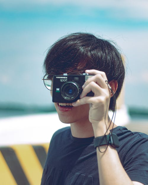 Unrecognizable young photographer in casual clothes and eyeglasses taking picture on vintage film camera on sunny day