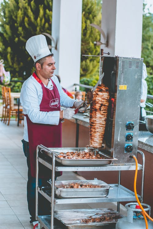 Ethnic male chef coking shawarma near counter in outdoor cafe