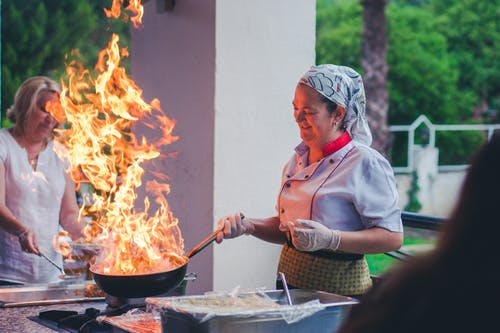Professional female cook roasting food with fire in pan during workshop
