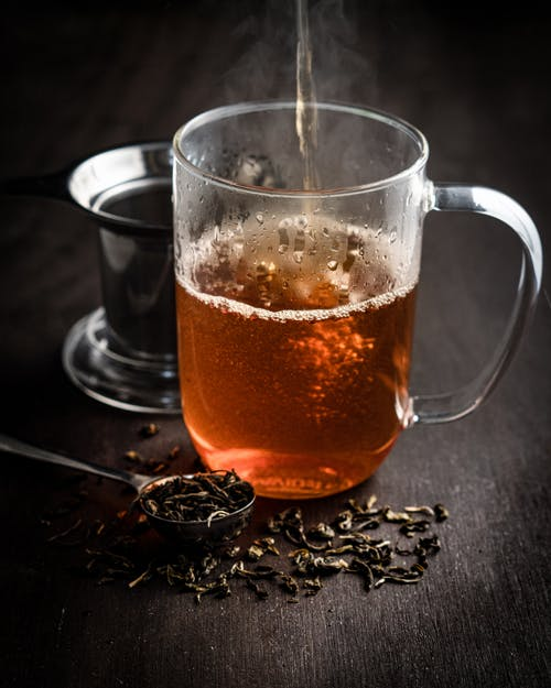 High angle of hot black tea in transparent mug served on wooden table near spoon and brewer