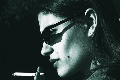 Side view of black and white thoughtful young female in sunglasses smoking cigarette on street on sunny day