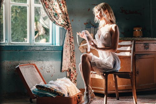 Sexy pensive young woman packing clothes in vintage suitcase
