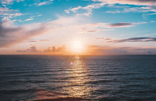 Picturesque scenery of sun shining over horizon and rippling wavy sea against cloudy blue sky at dusk