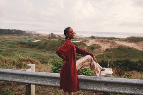 Side view of young stylish African American female traveler in trendy outfit and sunglasses sitting on road metal fence during trip near ocean against cloudy sky