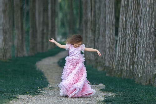 Little girl dancing in forest