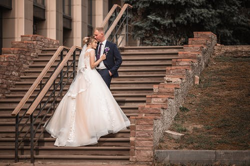Groom and fiancee in elegant suit embracing while standing on stone steps near long railing and building in daylight