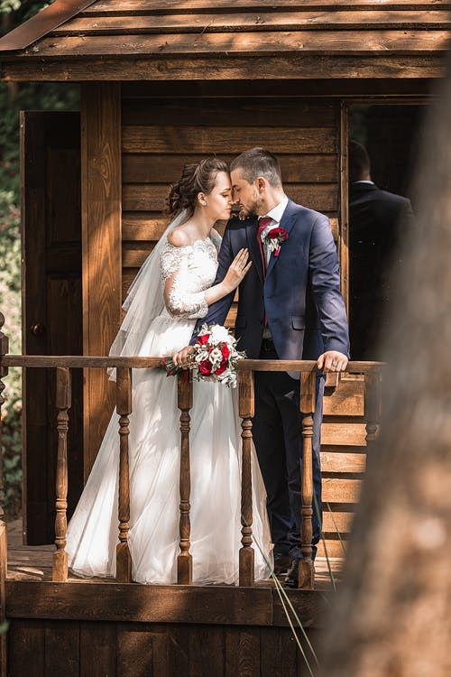 Romantic young bride and groom touching foreheads and embracing on balcony of wooden house on wedding day