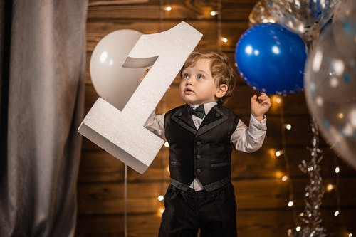 Happy little boy in elegant clothes smiling and playing with figure of his age while standing in cozy room with balloons