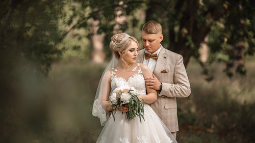 Beautiful newlyweds in elegant outfit and wedding bouquet standing in green valley