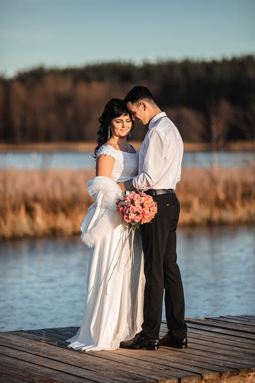 Happy newlywed couple hugging in love on wooden pier