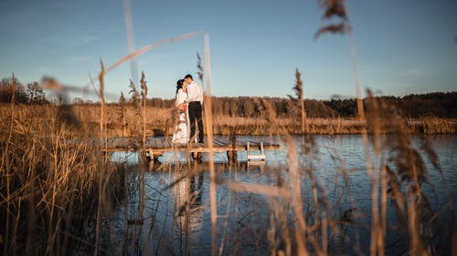 Married couple walking on pier over river