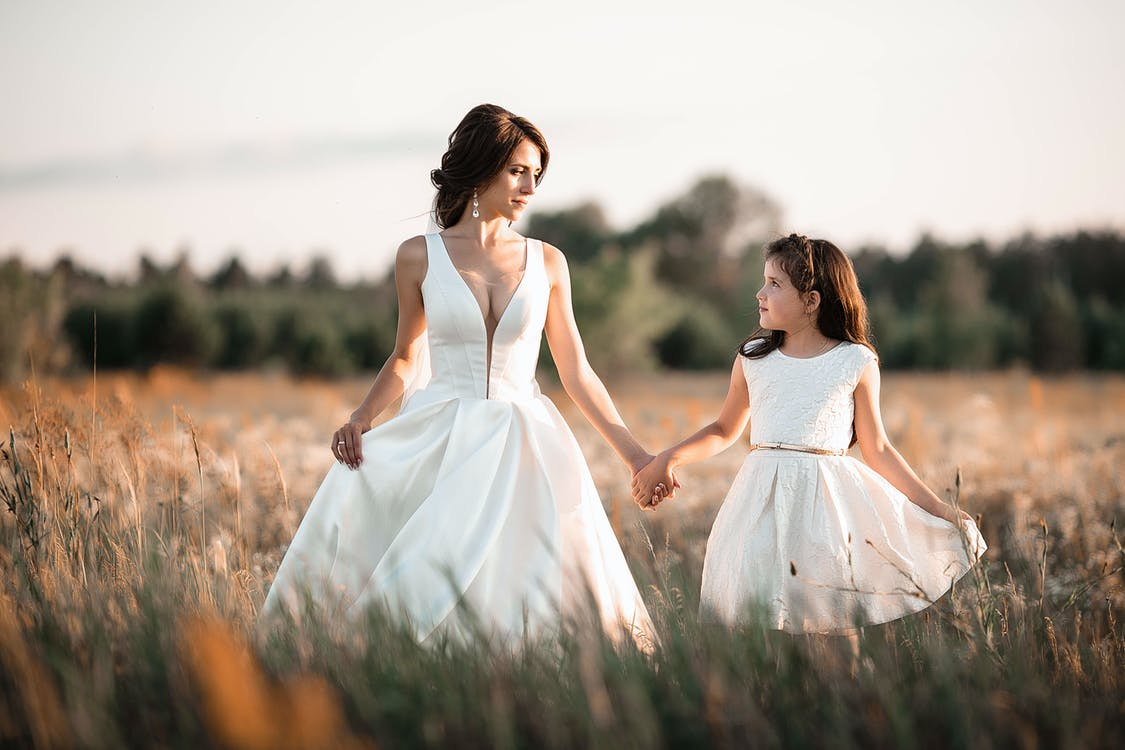 Happy woman in wedding dress with girl