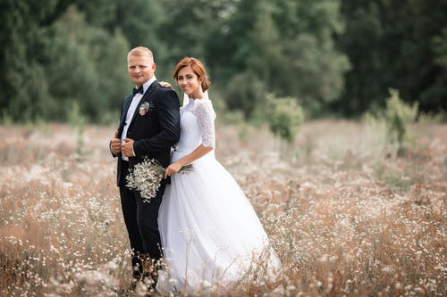 Full length of bride in white dress with bouquet standing near groom near green trees while spending time in field