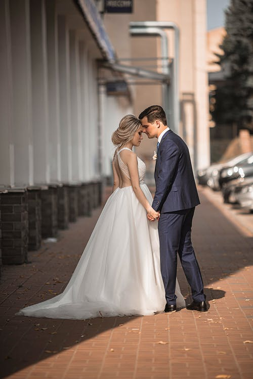 Newly married couple standing on pavement