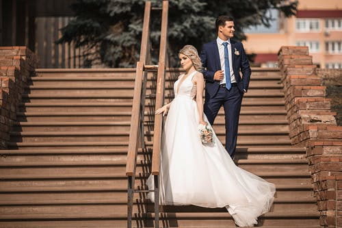 Newlywed couple standing on stairs