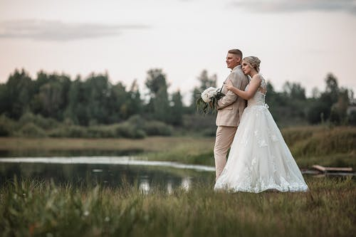 Full body of bride and groom hugging each other while standing on green meadow near lake in countryside in summer