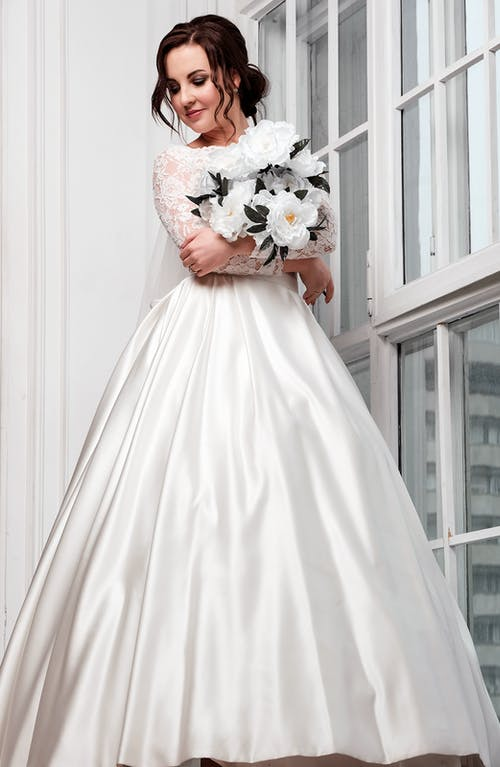 Full body of gorgeous woman in wedding dress standing with flowers in hands near window and looking away while preparing for event