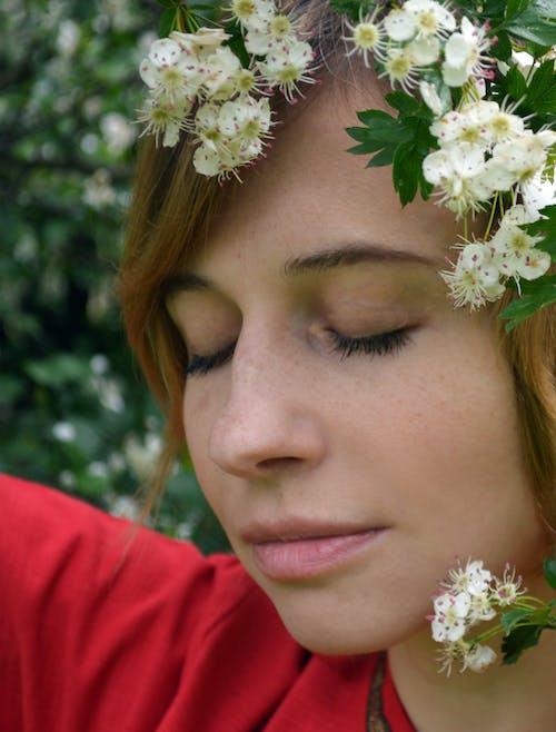 Tender woman standing under blooming flowers