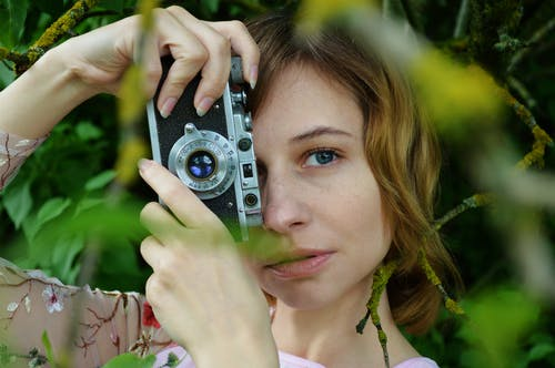 Cheerful female photographer with vintage camera standing under tree branches and taking pictures while looking at camera during summer time