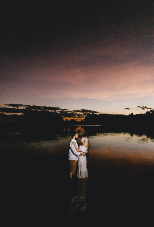 Sensual couple standing in lake water