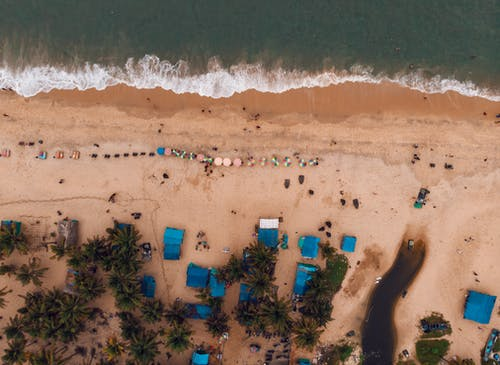 Drone view of resort with foamy waves and people chilling on sandy beach