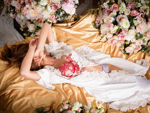 Woman in White Dress Lying on Bed With Pink Roses