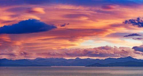 Majestic sunset sky above mountains and sea