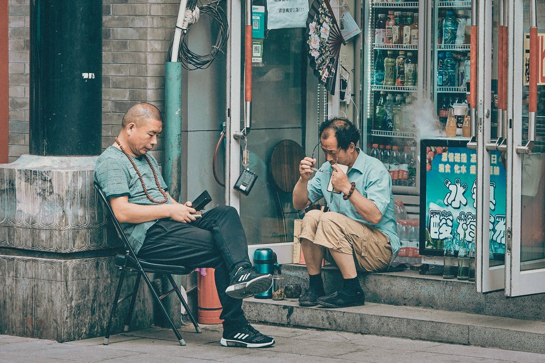 Man in Gray Dress Shirt Sitting on Chair