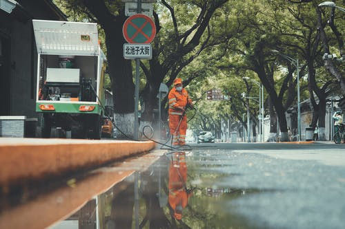 Man in Orange Jacket and Black Pants Standing on Wet Road