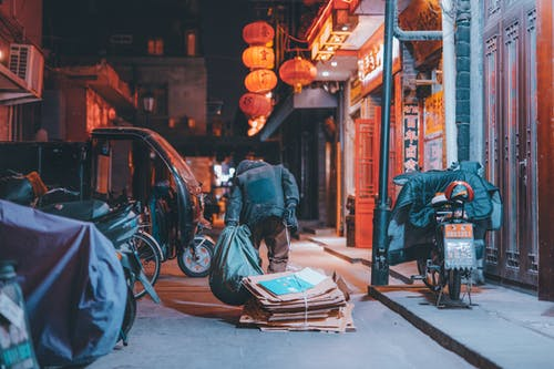 Man in Blue Jacket Sitting on Brown Wooden Cart during Nighttime