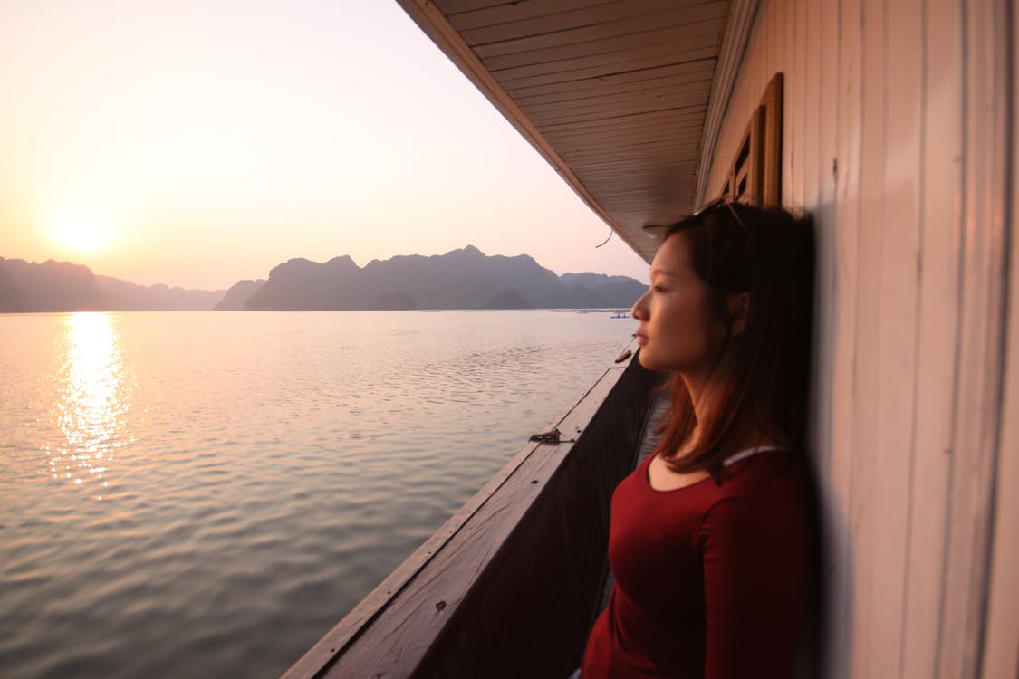 Woman Wearing Red Long-sleeved Scoop-neck Top Leaning on White Wall by the Sea during Golden Hour