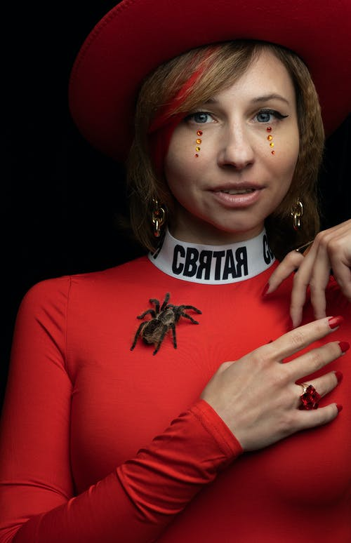 Eccentric young woman with spider and artistic makeup