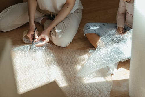 Woman in White Shirt and Blue Denim Jeans Sitting on Brown Carpet
