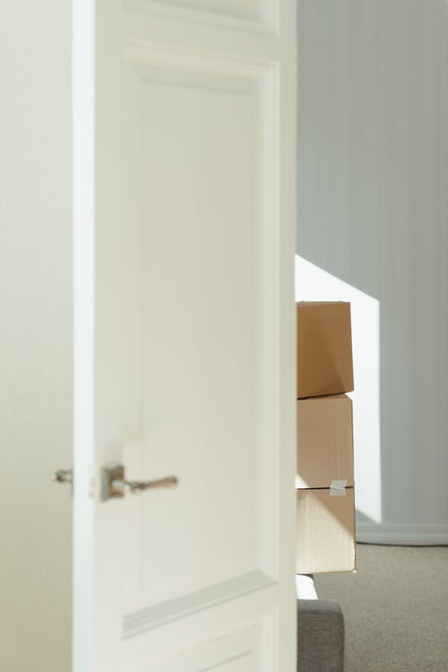White Wooden Door Near Brown Cardboard Box