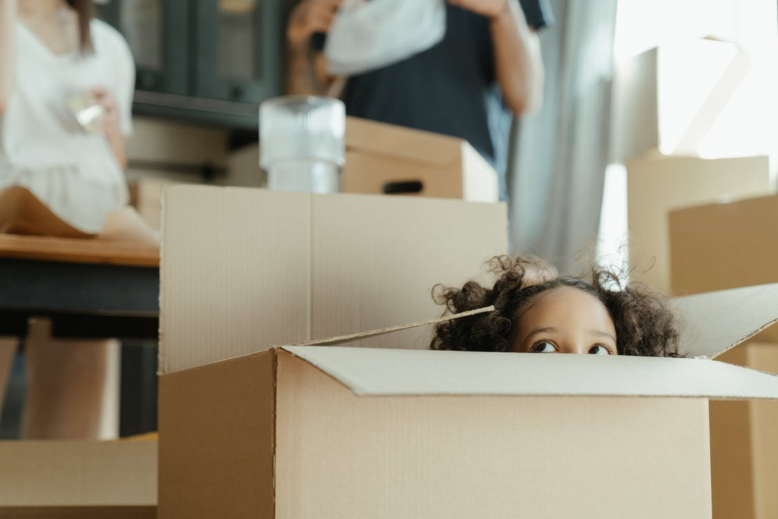 Woman in White Shirt Holding Brown Cardboard Box